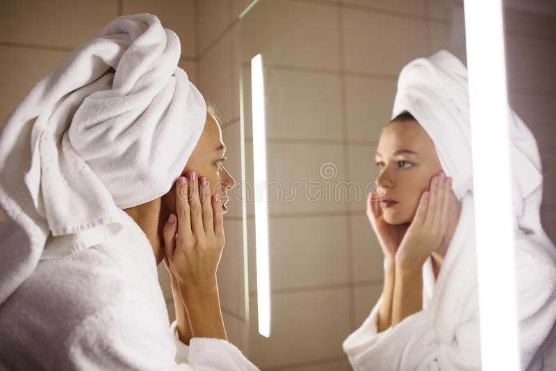 Vrouw die op haar spiegel kijken stock afbeelding