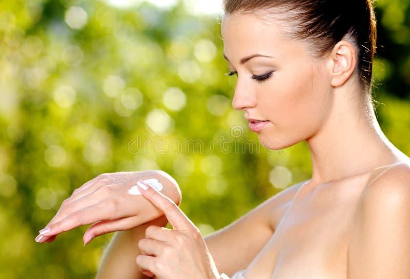 Vrouw die op hand kosmetische room van toepassing is stock foto's