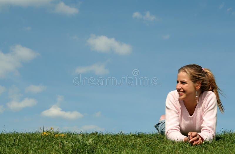 Vrouw die op het gras ligt royalty-vrije stock foto