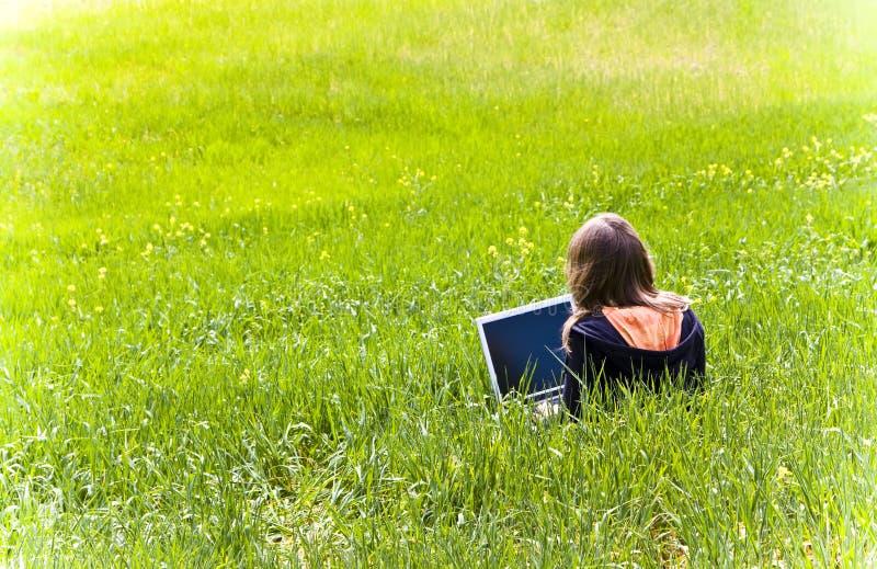 Vrouw die op het gras wordt verbonden stock fotografie