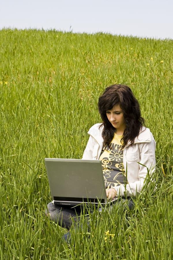 Vrouw die op het gras wordt verbonden royalty-vrije stock fotografie