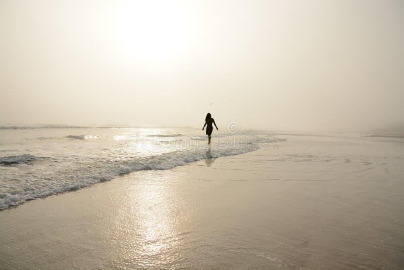 Vrouw die op het mistige strand lopen stock foto's