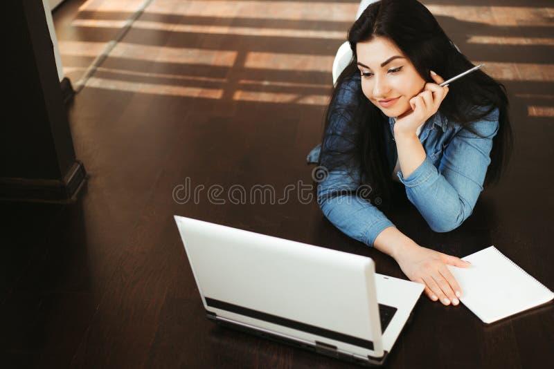 Vrouw die op het scherm van een laptop kijkt die van huis werkt royalty-vrije stock foto's