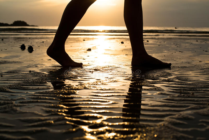 Vrouw die op het strand bij zonsondergang loopt royalty-vrije stock afbeelding