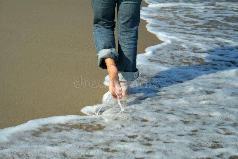 Vrouw die op het strand loopt stock foto's
