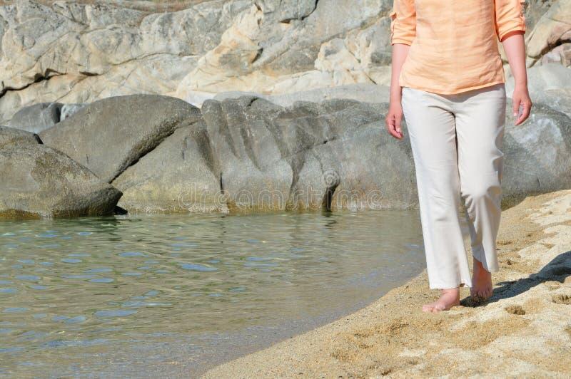 Vrouw die op het strand lopen stock afbeelding