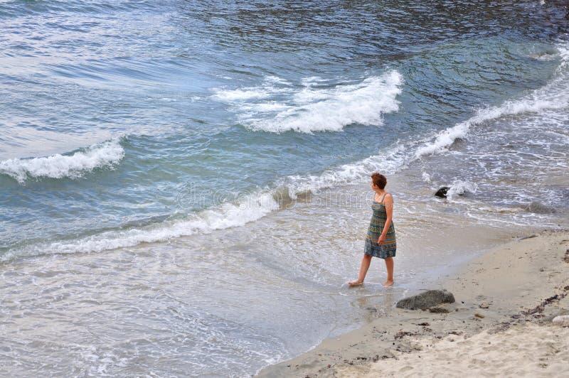 Vrouw die op het strand lopen royalty-vrije stock afbeeldingen