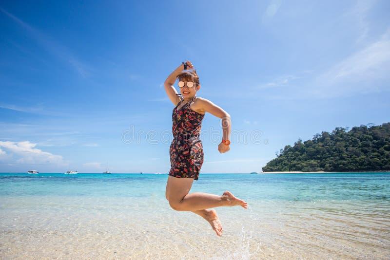 Vrouw die op het strand voor oceaan springen stock afbeeldingen