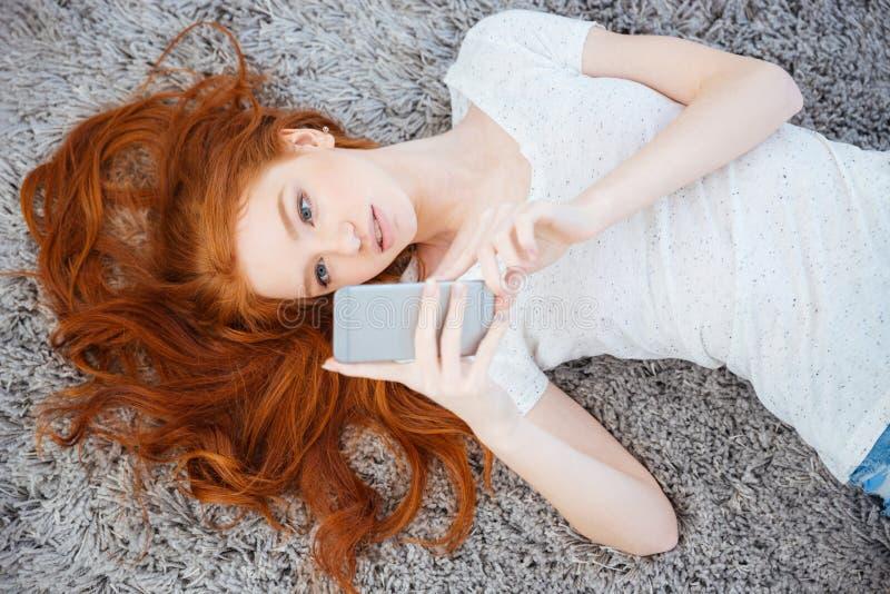 Vrouw die op het tapijt liggen en smartphone gebruiken royalty-vrije stock fotografie