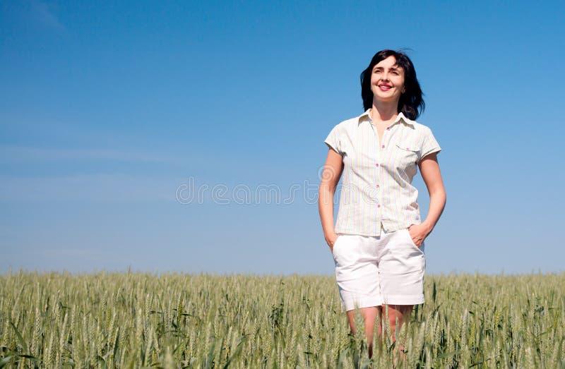 Vrouw die op het tarwegebied loopt stock afbeeldingen