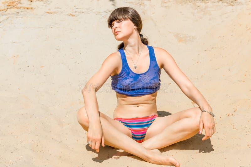 Vrouw die op het zand in lotusbloempositi zonnebaden stock foto