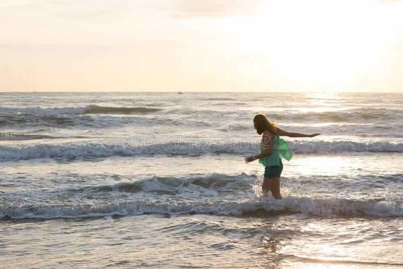 Vrouw die op het zandstrand lopen, zonneschijn in de ochtend stock foto's