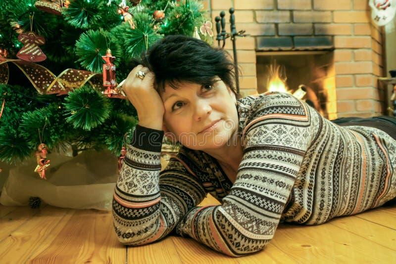 Vrouw die op houten vloer dichtbij open haard ligt stock fotografie