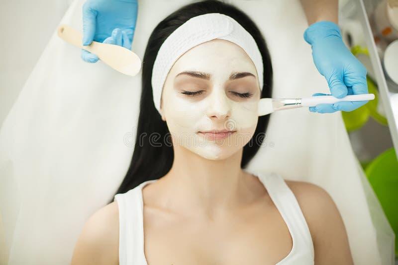 Vrouw die op massagelijst in health spa liggen terwijl het gezichtsmasker is royalty-vrije stock afbeelding