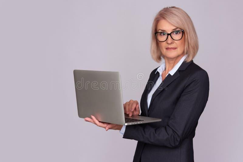 Vrouw die op middelbare leeftijd aan laptop werken royalty-vrije stock foto's