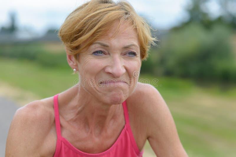 Vrouw die op middelbare leeftijd met een gedwongen uitdrukking grimassen trekken stock afbeelding