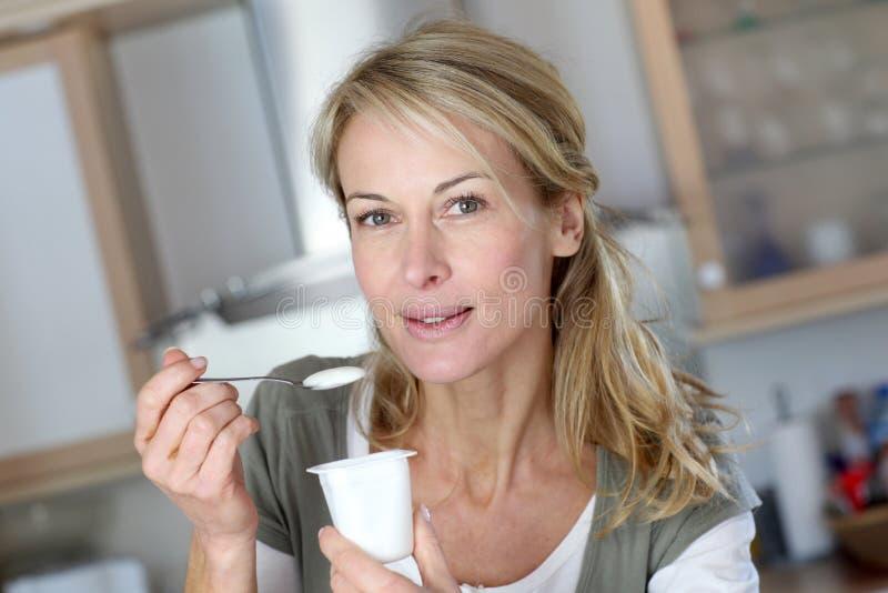 Vrouw die op middelbare leeftijd yoghurt eten stock foto's