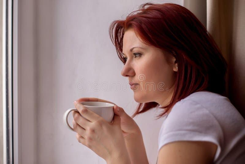 Vrouw die op middelbare leeftijd zorgvuldig het venster bekijken, die in handen witte mok thee of koffie houden Korte onderbrekin stock foto