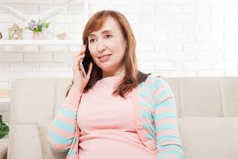 Vrouw die op mobiele telefoon spreekt Middenleeftijdsvrouw Exemplaarruimte en spot omhoog werkplaats royalty-vrije stock foto