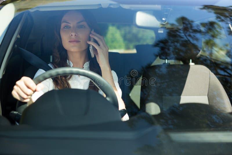 Vrouw die op mobiele telefoon spreken terwijl het drijven van een auto royalty-vrije stock afbeeldingen