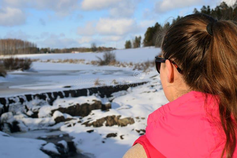 Vrouw die op mooie bevroren stroomversnelling letten stock foto's
