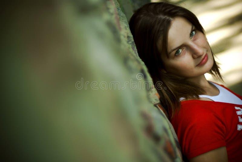 Vrouw die op muur leunt stock afbeelding