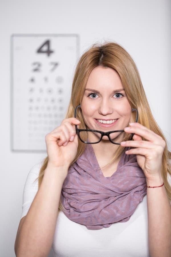 Vrouw die op Nieuwe Glazen proberen stock afbeeldingen