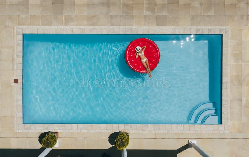 Vrouw die op opblaasbare matras in pool zonnebaden stock foto's