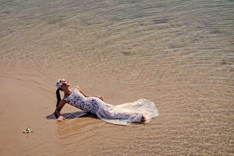 Vrouw die op overzees strand liggen Manier en schoonheid stock foto's
