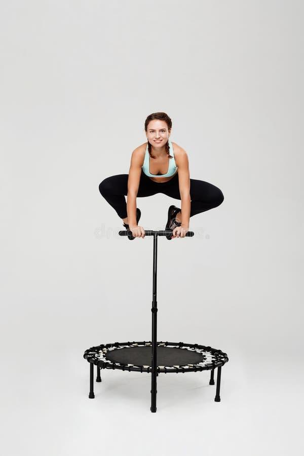 Vrouw die op rebounder met het buigen van knieën springen die handvat houden royalty-vrije stock foto