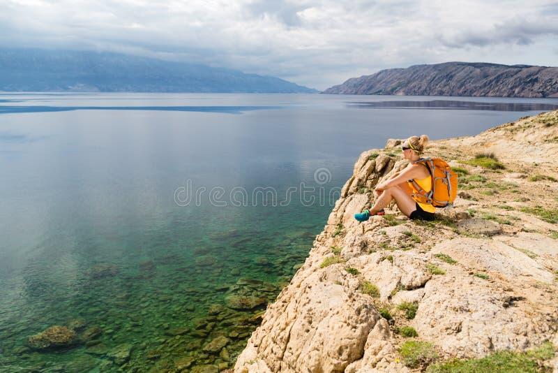Vrouw die op richel Adriatische Overzees, Rab Island, Kroatië overzien royalty-vrije stock fotografie
