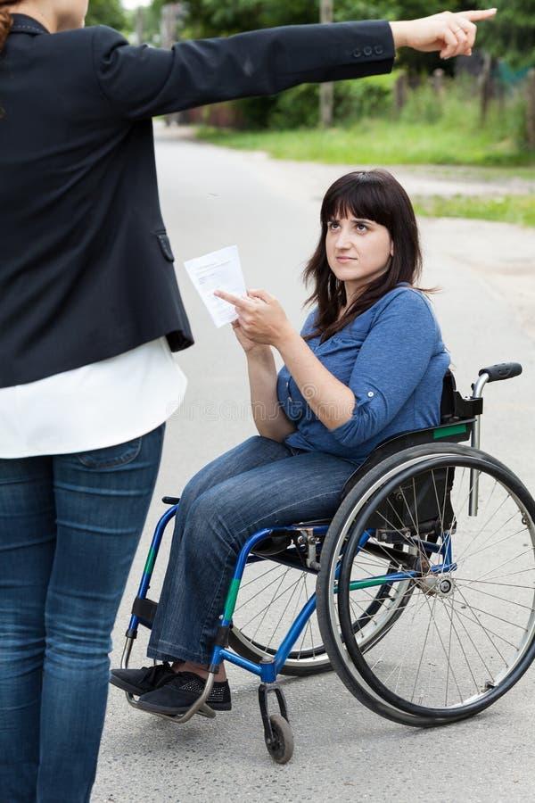 Vrouw die op rolstoel een voorbijganger vragen over richtingen stock afbeeldingen