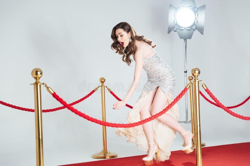 Vrouw die op rood tapijt vallen stock afbeelding