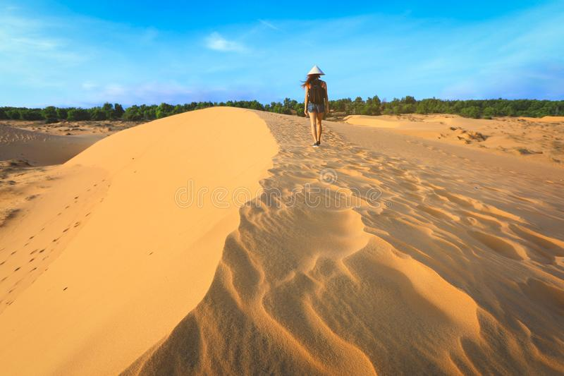 Vrouw die op rood zandduin lopen in Mui-Ne, Vietnam stock foto's