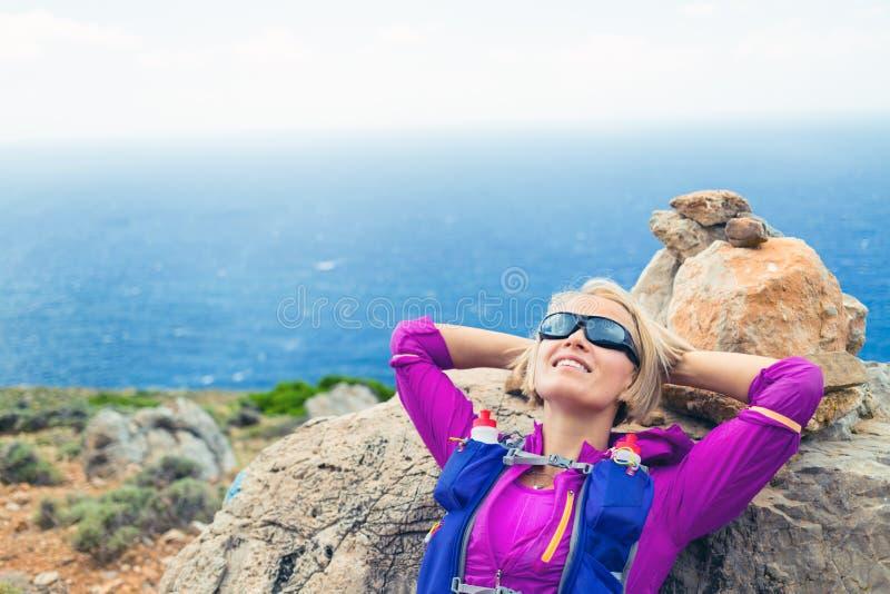 Vrouw die op rotsen, het Eiland van Kreta, Griekenland rusten stock afbeeldingen