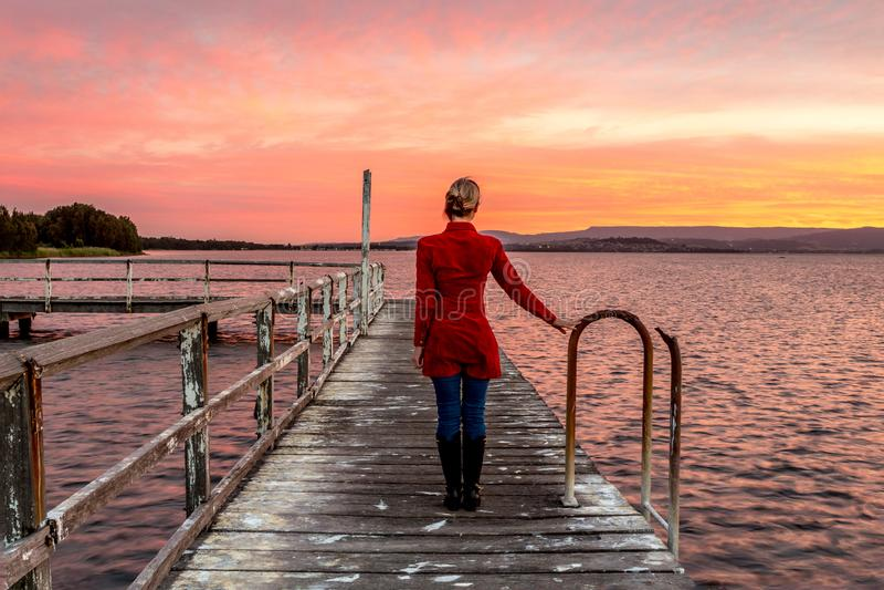 Vrouw die op rustieke houtpier op mooie zonsondergang letten stock foto's