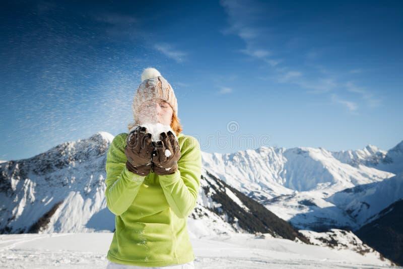 Vrouw die op sneeuw blaast royalty-vrije stock afbeeldingen