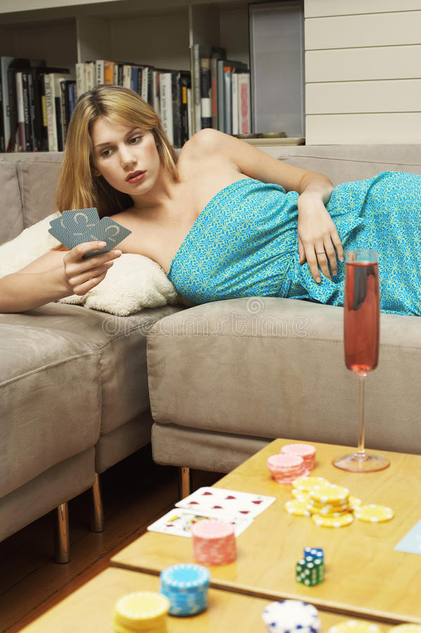 Vrouw die op Sofa And Playing Cards liggen stock foto's