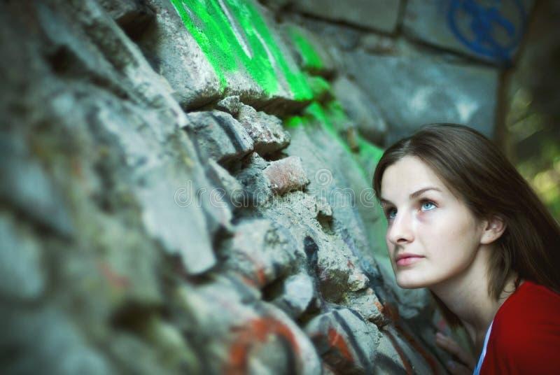 Vrouw die op steenmuur kijkt royalty-vrije stock afbeeldingen