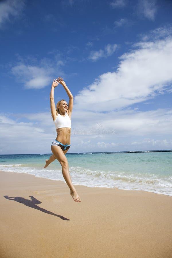Vrouw die op strand springt. stock afbeelding