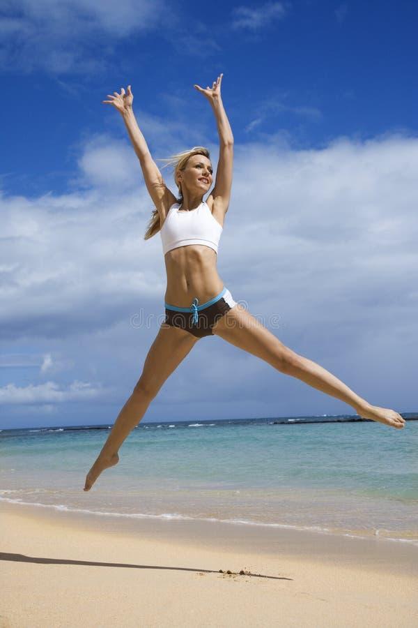Vrouw die op strand springt. stock fotografie