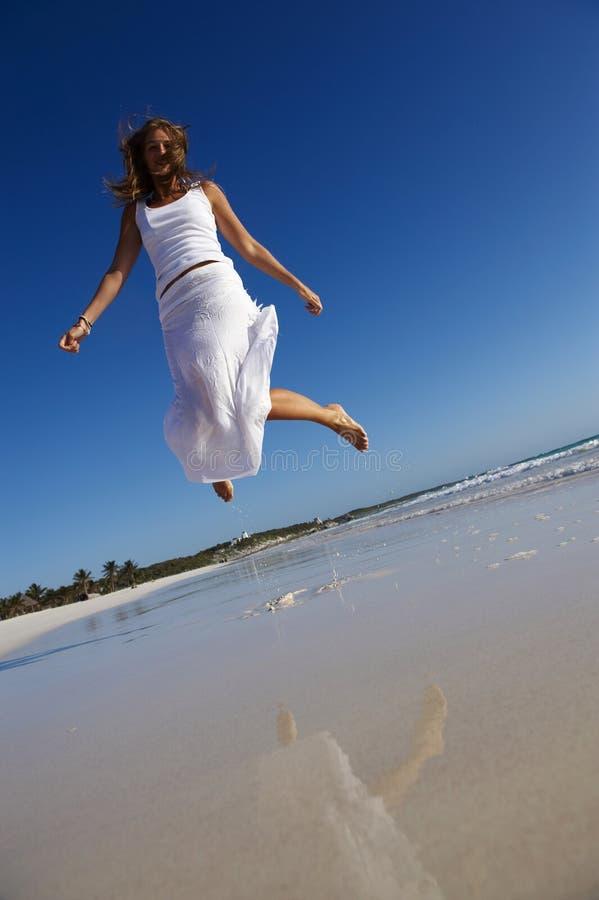 Vrouw die op strand springt royalty-vrije stock foto's