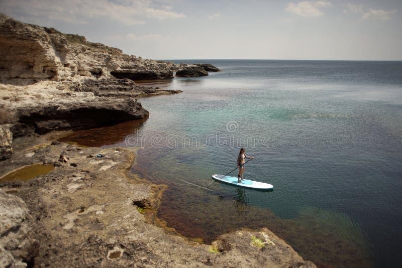 Vrouw die op SUP raad in een overzees paddelen stock foto