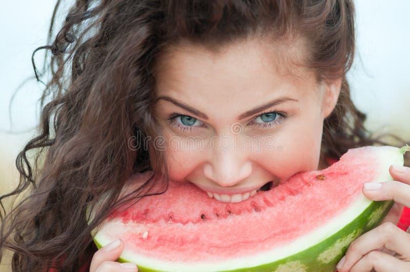Vrouw die op tarwegebied watermeloen eet. Picknick. royalty-vrije stock afbeeldingen