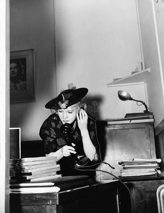 Vrouw die op telefoon in bureau spreken (Alle afgeschilderde personen leven niet langer en geen landgoed bestaat Leveranciersgara stock fotografie