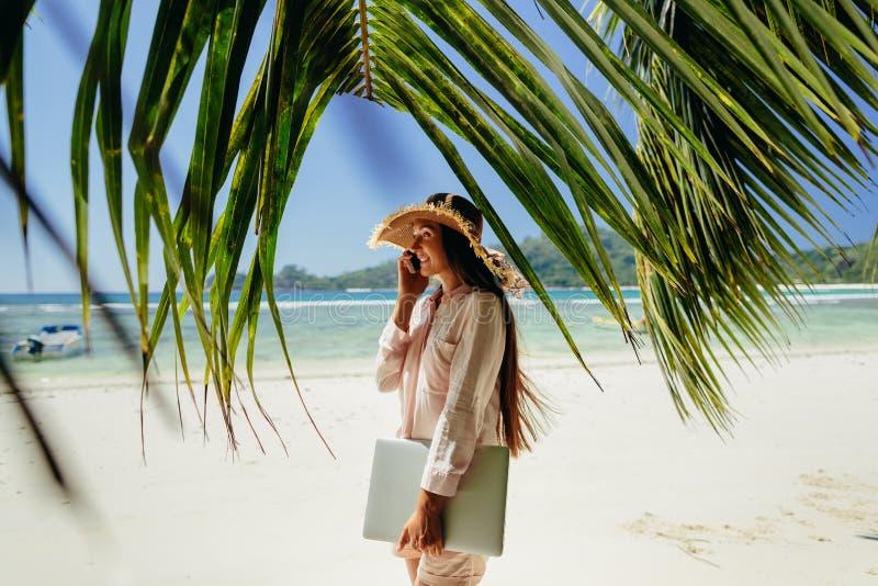 Vrouw die op telefoon met laptop op strand spreken royalty-vrije stock foto