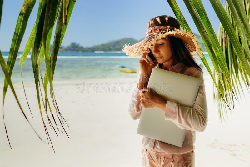 Vrouw die op telefoon met laptop op strand spreken stock afbeeldingen