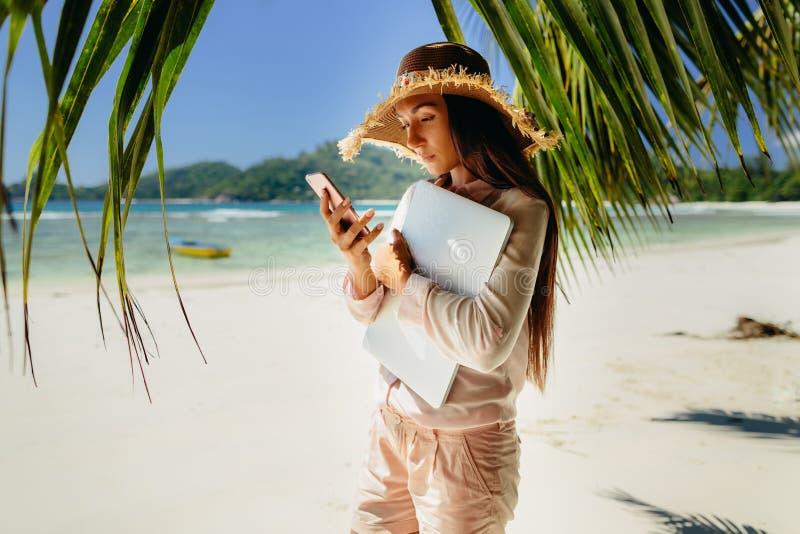 Vrouw die op telefoon met laptop op strand spreken royalty-vrije stock foto's