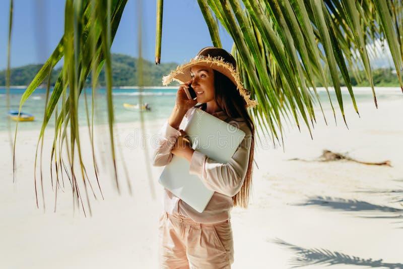Vrouw die op telefoon op strand in keerkringen spreken royalty-vrije stock fotografie