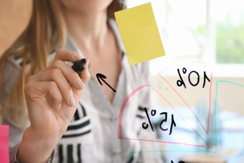 Vrouw die op transparante raad in conferentiezaal schrijven, close-up royalty-vrije stock foto's